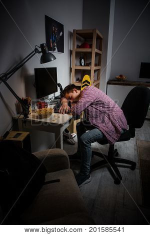 Teenage boy sleeping in front of computer. Boy falling asleep at the computer table, problem with computer addiction.