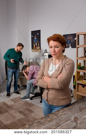Sad mother on foreground, father yelling on son on backdrop.Difficulties with transitional age of boy addicted to computer.