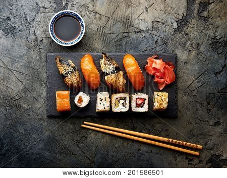 Variation of sushi and rolls on stone table. Sushi rolls, sashimi set with chopsticks. Top view with copy space.