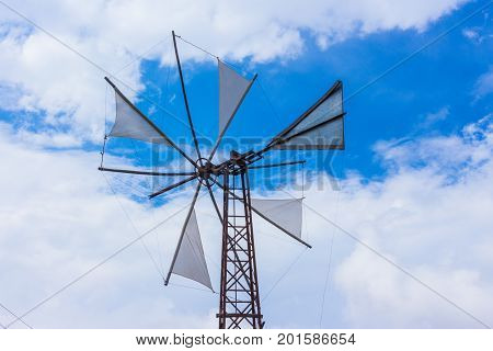 old traditional agricultural industrial greek steel windmill construction on blue sky in crete greece