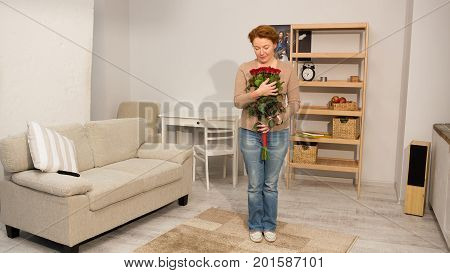 Happy mid aged woman holding bouquet of red roses. Foxy male in casual clothes standing at home in living room holding flowers.