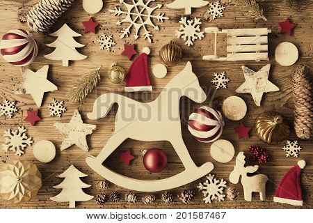 Flat Lay With Many Christmas Decoration, Like Rocking Horse, Ball, Sleigh, Fir Cone And Tree. Vintage Rustic Wooden Background With Instagram Filter