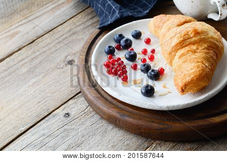 Fresh croissant, blueberries, red currants on white plate and cup of coffee on wooden tray. Continental breakfast