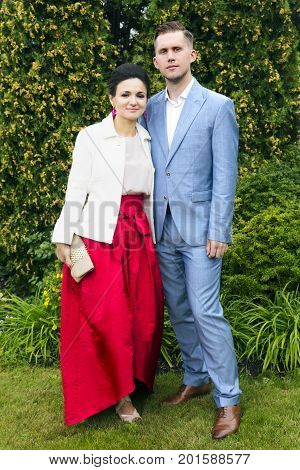 Happy young couple: man in elegant blue suit, women - in a white knitted jacket, red long skirt, beautiful make-up and hairstyle against the background of a green wall of thuja