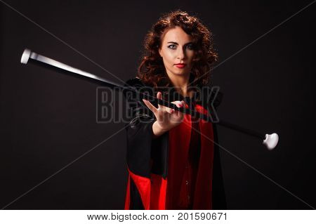 red-haired beautiful young woman in a red and black cape rotates in the fingers stick