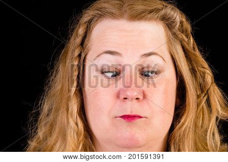 Portrait of attractive light overweighted mid aged woman showin crossed eyes - studio shot in front of black background