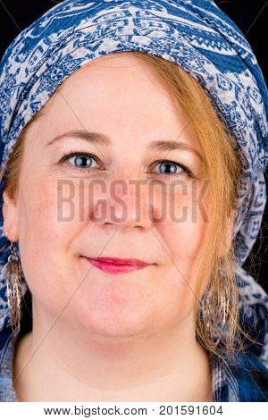 Portrait of a attractive european light overweighted red haired female with blue lumberjack shirt - view on head, studio shot in fron of black background