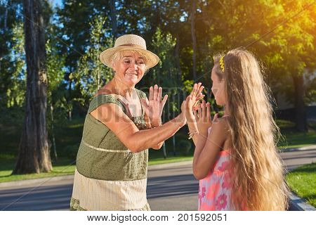 Hand clapping game. Grandma with granddaughter having fun.