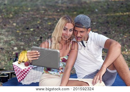 Boy And Girl Are Sitting And Looking At The Screen Of The Digital Tablet