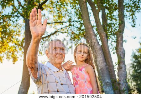 Girl with grandfather waving hands. People showing greeting gesture. Overcoming fear of aging.