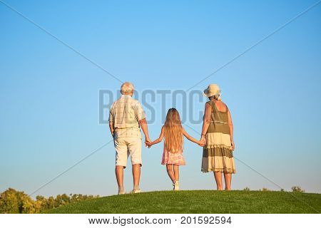 Child with grandparents, sky background. Seniors with grandchild back view.