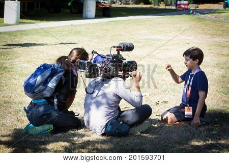 SALEM, WASHINGTON, USA - AUGUST 21, 2017: A young boy is interviewed and videotaped by PBS Nova team  on the lawn of Willamette University after solar eclipse.