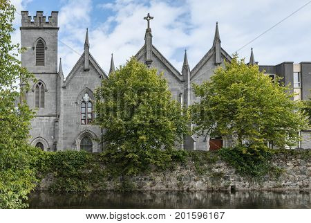 Galway Ireland - August 3 2017: The gray stone Saint Vincent's Convent of Mercy with its towers and crosses stands behind a couple of green trees along the Corrib River. Blue white skies.