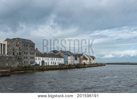 Galway Ireland - August 3 2017: The Long Walk Quay of the old port seen from across the dark Corrib River mouth. All under heavy storm sky. Image leads the viewer to the Atlantic Ocean and Nimmo's Pier.