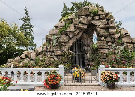 Galway Ireland - August 3 2017: Saint Mary's grotto in the garden of Saint Mary's Dominican church under silver sky and surrounded by flowers. Statue of the Lady.