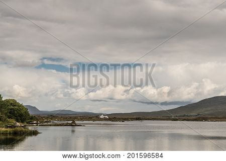 Connemara County Ireland - August 4 2017: Wide view of Furnace Lake under a gray sky with one blue patch and pronounced low clouds. Green hills and a white house on the horizon.