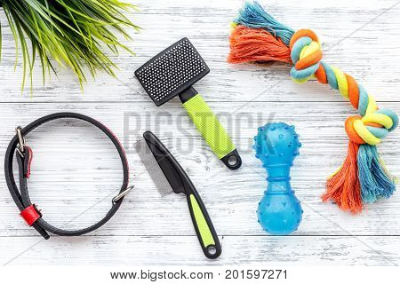 grooming equipment with toys for care and training pet on white wooden desk background top view