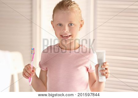 Cute little girl with toothbrush and paste at home. Cleaning teeth concept