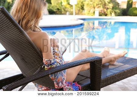 Beautiful young woman reading book while relaxing on sun lounger near swimming pool