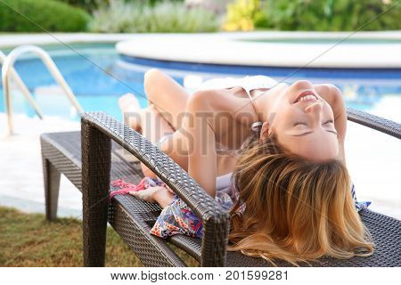 Beautiful young woman relaxing on sun lounger near swimming pool