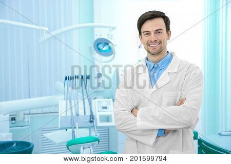 Young male dentist in light office