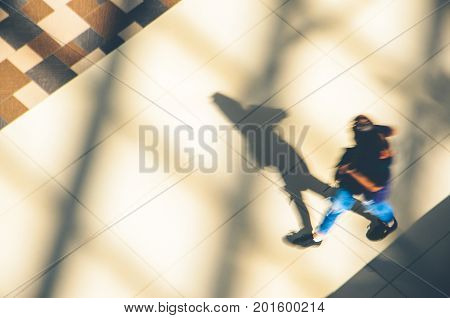 Silhouette of a walking woman with long shadow from above. Abstract background of blur in motion figure of a girl
