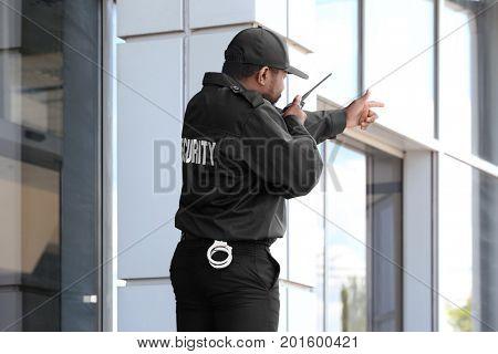 Male security guard using portable radio transmitter near big modern building