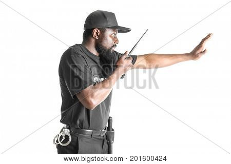 Male security guard showing stop gesture while using portable radio transmitter, on white background