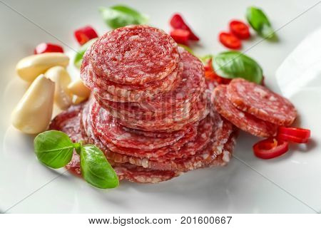 Delicious sliced sausage with garlic and chili pepper on plate