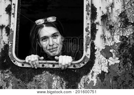 Attractive young woman looking out of the window metal caboose. Black and white portrait.