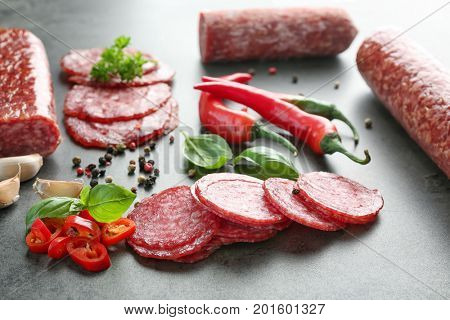 Delicious sliced sausage and chili pepper on table
