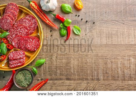 Plate with sliced different sausages and chili pepper on table