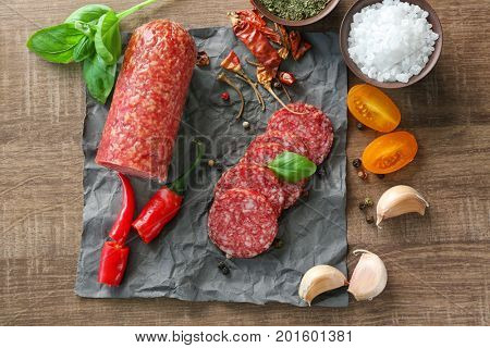 Composition with sliced sausage and chili pepper on table