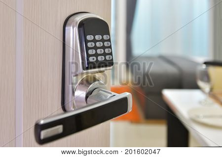 Electronic door access control system machine with number password door..Half opened door handle closeup entrance to a living room.Door lock with keys number.