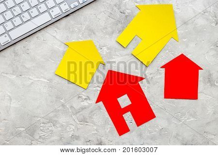 work desk with keyboard and paper house figures for selling house set stone background top view space for text