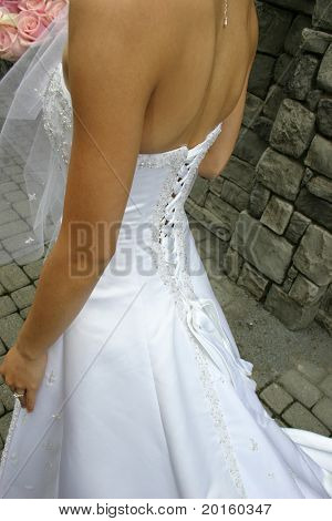 back and side of bride with bouquet against brick