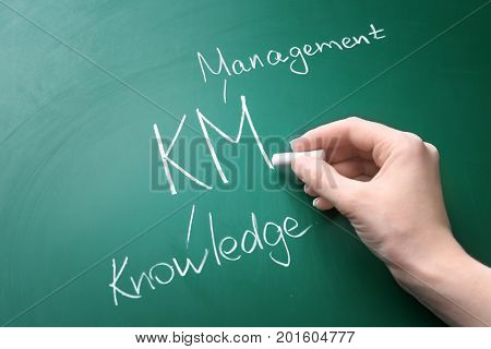Female hand writing management abbreviation KM with its full form on chalk board