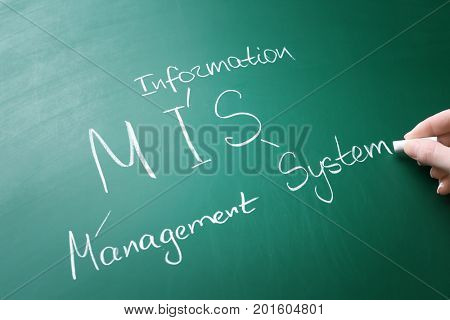 Female hand writing management abbreviation MIS with its full form on chalk board