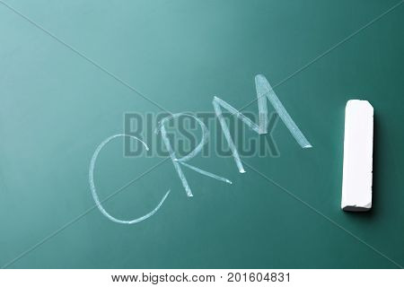 Management abbreviation CRM written on chalk board