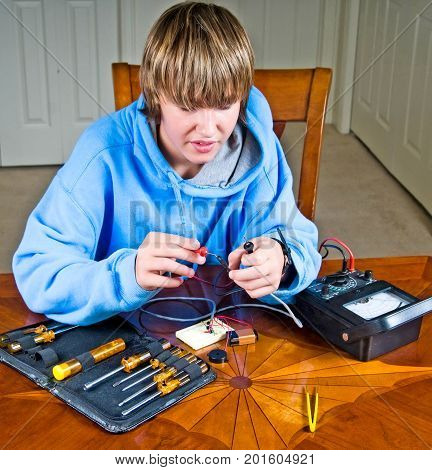 Teen boy uses an ohmmeter to measure resistance across a circuit for a science project.