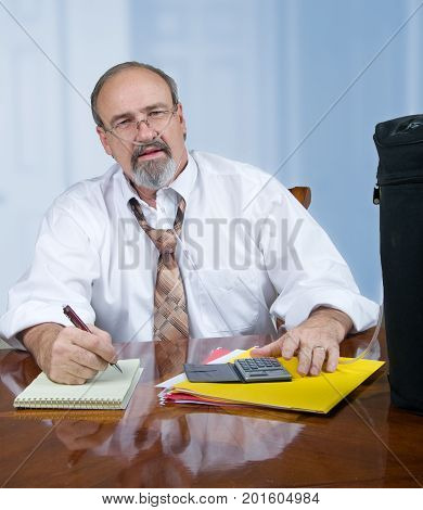 Adult male working with files at a desk while wearing an O2 canula to help his breathing.