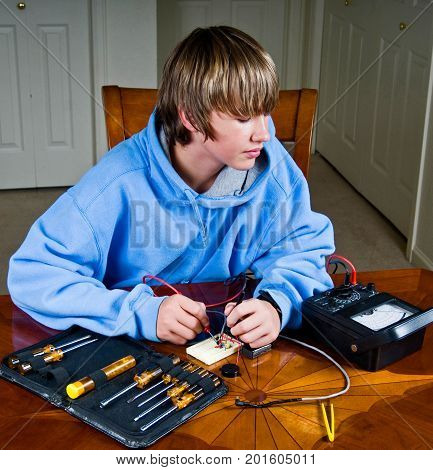 Teenage boy measures voltage across a circuit in a science project.