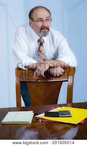 A businessman leans on a chair back while he engages with co-workers.