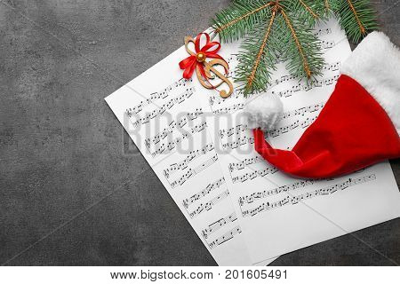 Beautiful composition with decorations and music sheets on grey background. Christmas songs concept