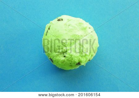Ball of delicious mint chocolate chip ice cream on color background