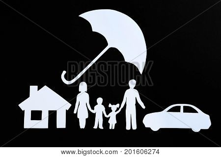 Paper silhouette of family, umbrella, house and car on black background. Life insurance concept
