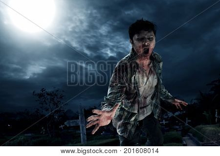 Scary zombie walking on graveyard at night