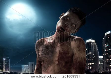 Scary zombie walking on city building at night