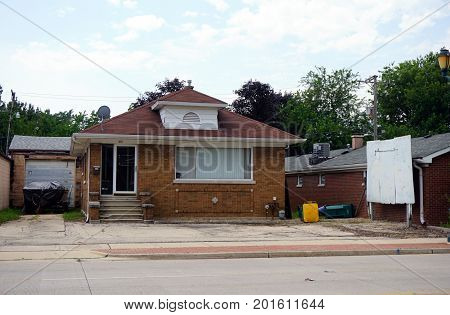 JOLIET, ILLINOIS / UNITED STATES - JULY 20, 2017: A brown brick single family home with a broken picture window, on Plainfield Road in Joliet.