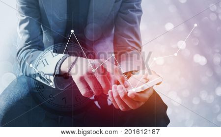 Double exposure of businessman holding smart phone with a row of stack money coins and analog clock with business graph information diagram concept for business finances and saving money.